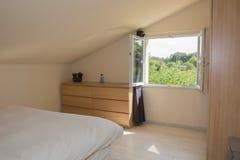 Camera da letto luminosa in soffitta con il grande letto immagine stock libera da diritti