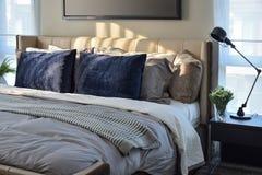 Camera da letto moderna con i cuscini blu e la lampada nera sulla tavola Fotografie Stock Libere da Diritti