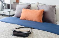Camera da letto moderna con i cuscini variopinti e la borsa della femmina sul letto fotografia stock libera da diritti