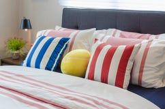 Camera da letto moderna con i cuscini variopinti sul letto e sulla fuga nera moderna immagini stock