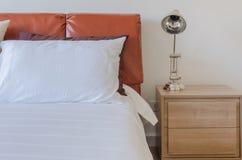 Camera da letto moderna con il letto marrone di cuoio e lampada moderna su di legno fotografia stock