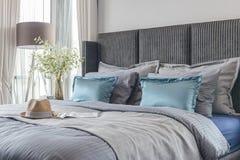 Camera da letto moderna con il tono del letto di colore e l'insieme neri dei cuscini immagine stock libera da diritti