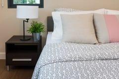 Camera da letto moderna con la lampada bianca e le piante sulla tavola Immagini Stock