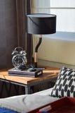 Camera da letto moderna con la lampada e la sveglia nere sulla tavola di legno Immagini Stock