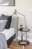 Camera da letto moderna con la lampada grigia moderna fotografia stock