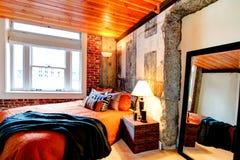Camera da letto moderna con un muro di cemento rotto Immagini Stock Libere da Diritti