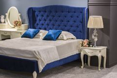 Camera da letto reale di lusso nello stile antico con il letto blu del velluto ed il comodino bianco immagini stock libere da diritti