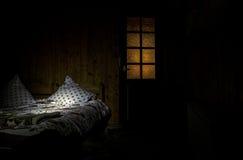 Camera da letto scura con le luci surreali dei cuscini e del letto e porta di legno con la finestra fotografie stock