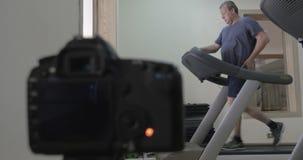 Camera de schoten van mens maken die lopend op tredmolen stock videobeelden