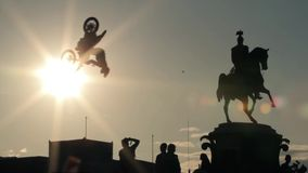 Silhouettes of monument, group of people underneath and extreme jumping bikers. stock video footage