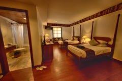 Camera di albergo con il letto gemellato e la toilette immagine stock