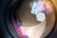 Camera diaphragm aperture with flare and reflection on lens. Camera diaphragm blades with 2.8 aperture with flare and reflection on lens Royalty Free Stock Images