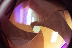 Camera diaphragm aperture with flare and reflection on lens. Golden blades of amera diaphragm aperture with flare and reflection on lens Royalty Free Stock Photography