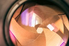 Camera diaphragm aperture with golden flare and reflection on lens. Camera diaphragm aperture with golden blades with flare and reflection on lens Royalty Free Stock Images
