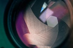Camera diaphragm aperture with purple yellow flare and reflection on lens. With blockbuster green frame Royalty Free Stock Photography