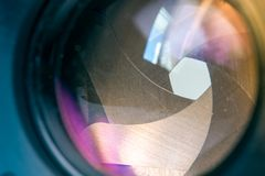 Camera diaphragm aperture with window reflection flare and reflection on lens. Camera diaphragm aperture with window reflection flare and purple and yellow Royalty Free Stock Photography