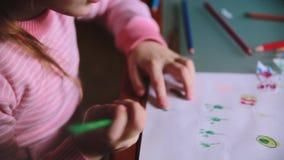 Camera die net over leuk Kaukasisch meisje glijden die op papier met verschillende kleurenpotloden bij een lijstclose-up trekken stock videobeelden