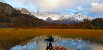 A camera in front of the Laguna Capri and Mount Fitz Roy covered by clouds, Argentina stock photos