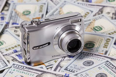 Camera on the dollars. Included silver camera with the lens lying on the dollar bills Stock Photo