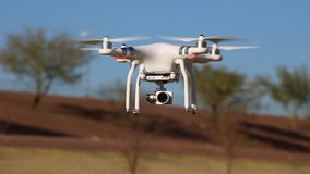 Camera Drone Flying at a Park. Picture of a white camera drone flying in blue sky Royalty Free Stock Image