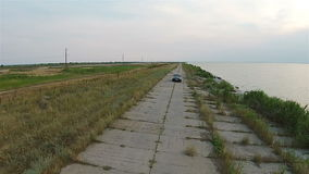 The camera on the drone tracks the car, which rides along the embankment near the sea stock footage