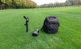 Camera equipment and gimbal on grass in city park. stock images