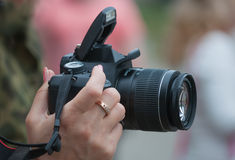 Camera in a female hand. Outdoors Stock Images