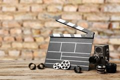 Camera and filmstrip on table. Movie camera cinematography concept creative lens stock photography