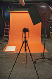 Camera, Fine Art and Commercial Photography Studio. A camera sits on a tripod in a professional and fine art photography studio and space. An orange backdrop royalty free stock photos