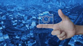 Camera flat icon on finger over modern city tower, street, expressway and skyscraper, Business camera service shop concept. Camera flat icon on finger over stock footage