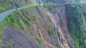 Camera Flies along Highway on Steep Cliff and Waterfall stock footage
