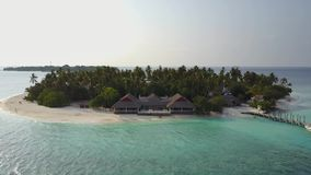 The camera flies around the small round tropical atoll island resort hotel with white sand palm trees and turquoise stock video