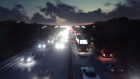The camera flies over heavy traffic. Cars with lights on go through the city at night. Produced in 4K stock footage