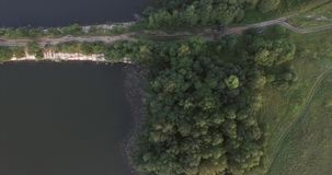 The camera flies over the river at the stone bridge. You can see the streets, cars, trees, and river beach. The tops of. Moscow oblast, Russia. The camera flies stock video