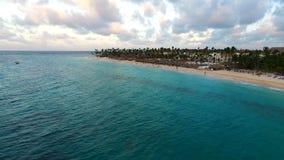 The camera flies over the sea along the sandy beach. The camera flies over the blue sea along the sandy beach stock footage