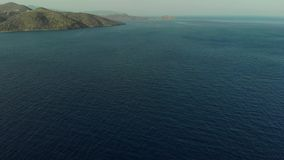 The camera flies over the sea towards the island. The frame rises from the sea to the island. The island in the distance