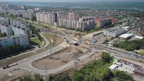 Camera flying over dormitory of big modern russian city, near construction of modern junction. Difficult car traffic stock video footage