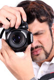 Camera Focus. A young Indian photographer closing his eye to focus his camera accurately Royalty Free Stock Photography
