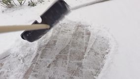 Camera focuses on the woman`s arms with snow shovel. In winter day stock video