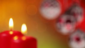 Camera focusing from beautiful christmas baubles to burning xmas candles stock video footage
