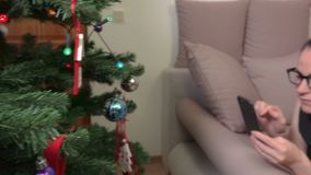 Camera focusing on Christmas decoration on Christmas tree then on woman who relaxing on sofa. In room stock footage
