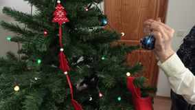 Camera follow hand with Christmas decoration near Christmas tree. In room stock video footage