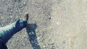 Camera following feet walking over rough terrain stock video