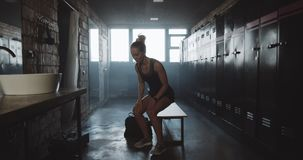 Camera follows athletic European woman entering dark gym locker room, sitting along feeling tired and upset slow motion. Failure and motivation crisis stock footage