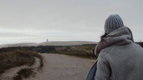 Camera follows beautiful European tourist woman in winter coat walk to far away overcast beach lighthouse slow motion. stock video footage