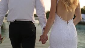 Camera follows bride and groom as they walk to ceremony along shore line near bungalows on bridge at luxury resort on stock video