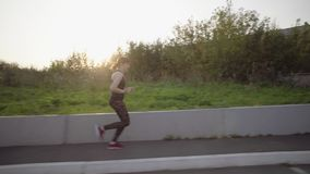 Young woman running on urban area. Camera follows female athlete runs in an urban environment near wreckage of walls and abandoned building. Sporty girl in dark stock video