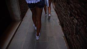 Camera follows girl legs walking on old narrow shady street