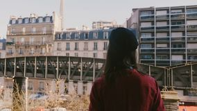 Camera follows happy professional photographer woman taking a photo of majestic Eiffel Tower view in Paris from balcony. stock video footage