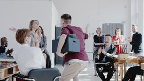 Camera follows happy successful male manager giving high fives to office team colleagues with a box slow motion RED EPIC